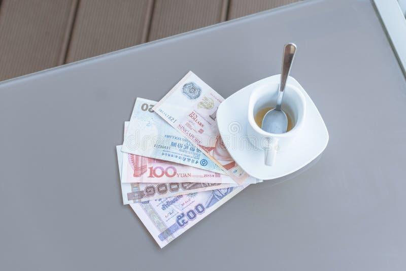 Dólar de Hong Kong, de Indonesia, de Malasia, del tailandés, de Singapur y taza de café vacía en una tabla de cristal de café al  imágenes de archivo libres de regalías