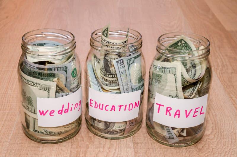 Dólar en el tarro de cristal con la casa, coche, educación, casandose concepto financiero de la etiqueta del viaje fotos de archivo libres de regalías