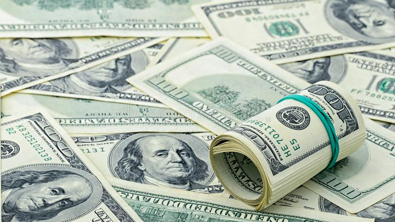 Dólar rodado ciento en billete de dólar americano del dinero del fondo Muchos billete de banco de los E.E.U.U. 100 fotografía de archivo