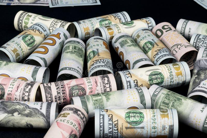 Dólar Rollo de los billetes de banco del dólar en otras posiciones Moneda americana de los E.E.U.U. en tablero negro Rollos ameri imagenes de archivo