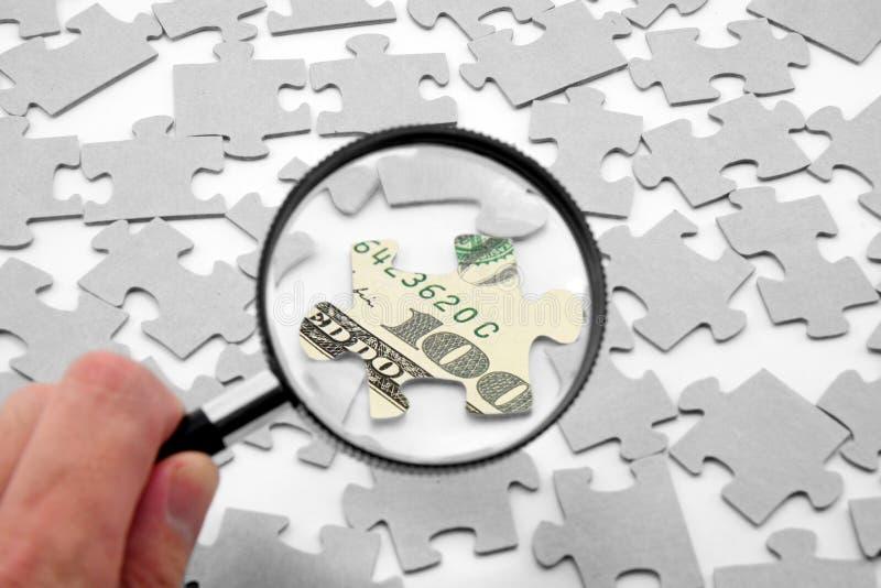 Dólar rompecabezas y lupa imágenes de archivo libres de regalías