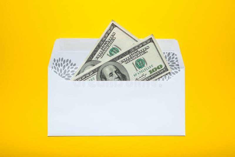 Dólares americanos en el sobre blanco aislado en fondo amarillo imagenes de archivo