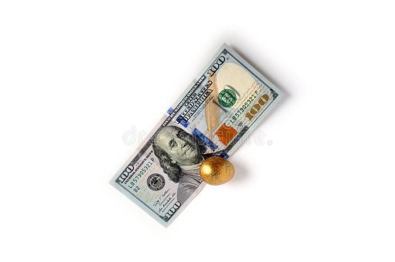 Dólares americanos y un huevo de oro Cientos billetes de dólar y un huevo de oro fotos de archivo