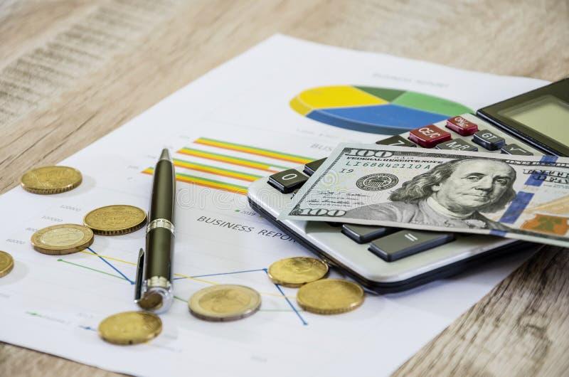 Dólares, calculadora, pena e moedas na carta de negócio fotografia de stock royalty free