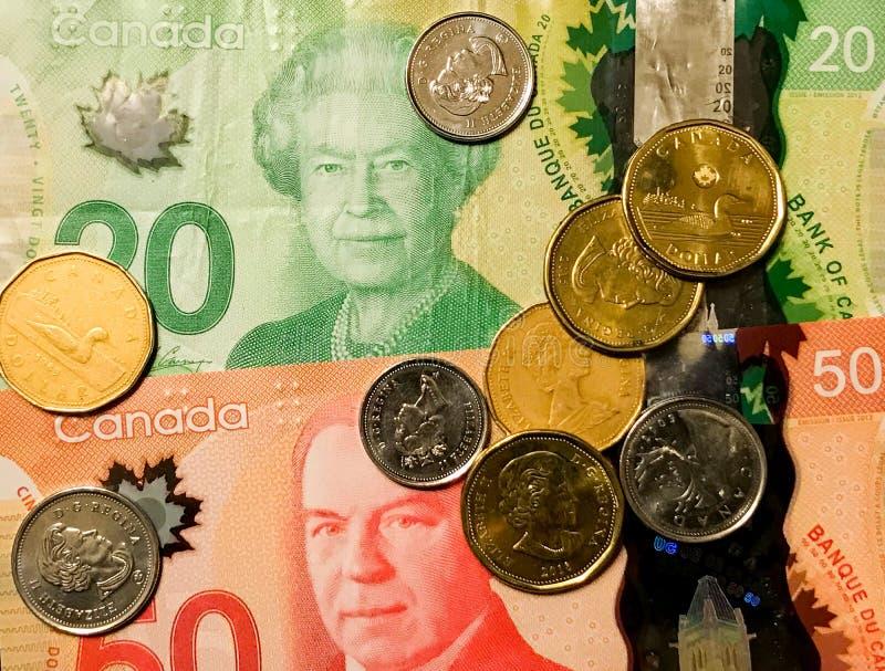 Dólares canadienses y monedas fotos de archivo