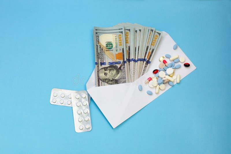 Dólares da moeda no envelope contra tabuletas dispersadas, comprimidos, cápsulas, compra das medicamentações imagens de stock