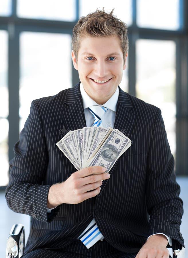 Dólares da terra arrendada do homem de negócios fotografia de stock