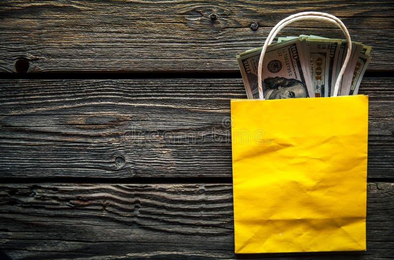 Dólares da vara fora do saco de compras, comprando Dinheiro americano, feriados foto de stock royalty free