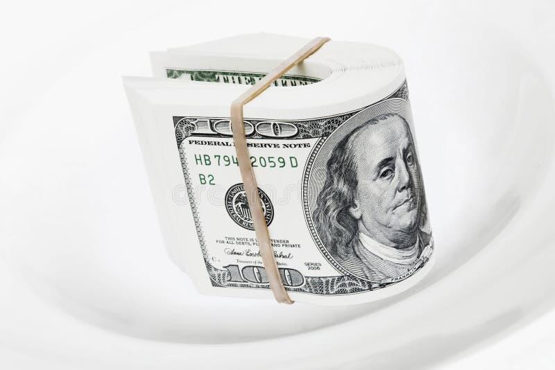 Dólares de notas sobre la placa blanca fotografía de archivo
