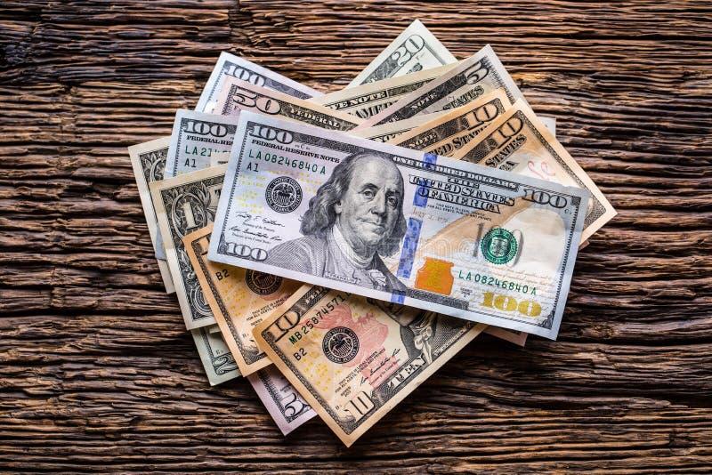 Dólares de primer de los billetes de banco en la tabla de roble rústica Dólares del americano del dinero del efectivo Opinión del foto de archivo
