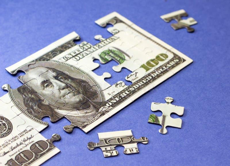 Dólares de rompecabezas Concepto de finanzas y de ahorros fotos de archivo libres de regalías