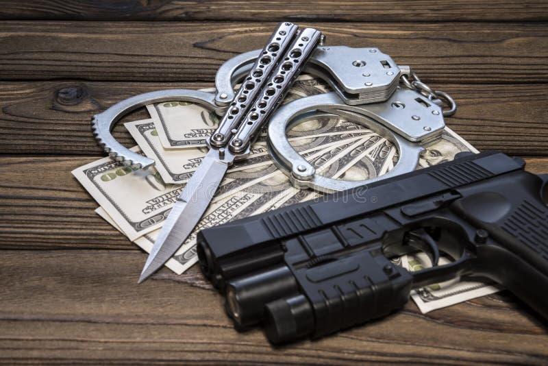 Dólares del cuchillo y del dinero del arma de las esposas imagenes de archivo