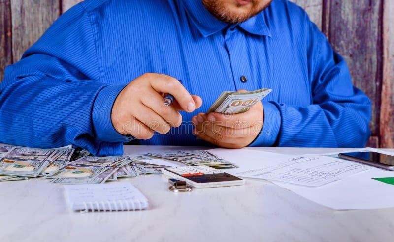 Dólares del recuento de la mano el hombre cuenta las nuevas cuentas del ciento-dólar del dinero fotografía de archivo