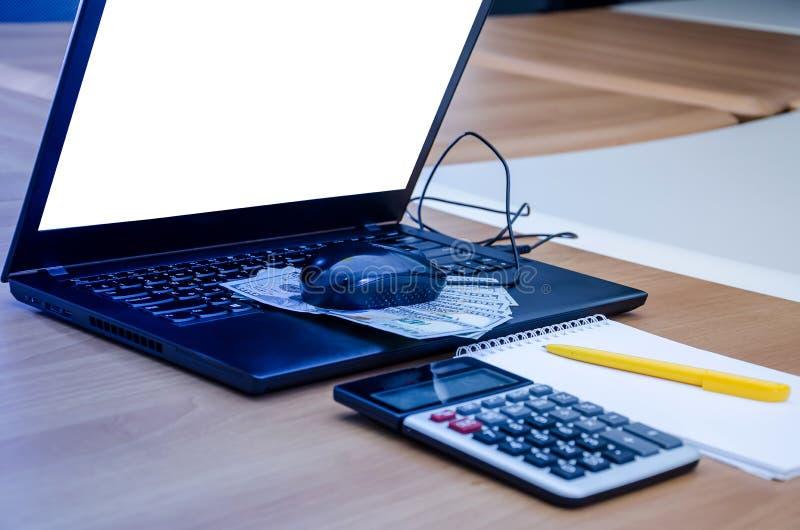 Dólares do rato do computador no teclado do portátil Pena, calculadora e caderno na tabela Um portátil com uma tela branca fotografia de stock