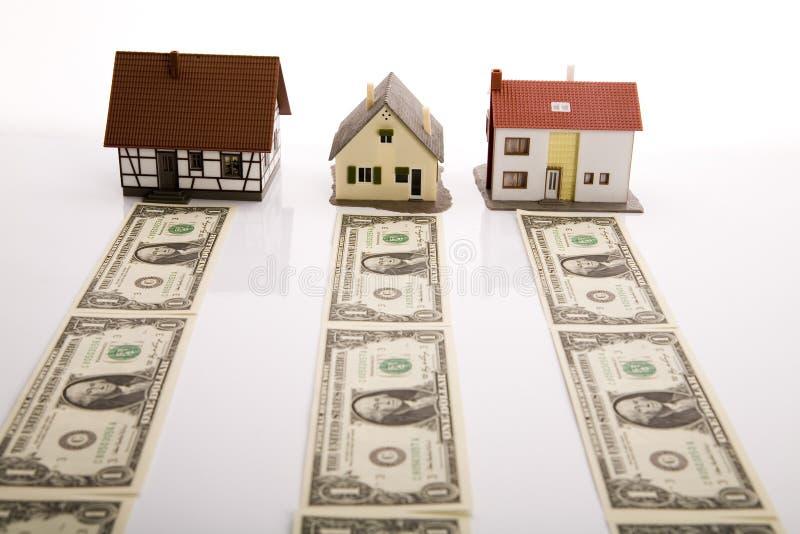 Dólares e casas imagens de stock