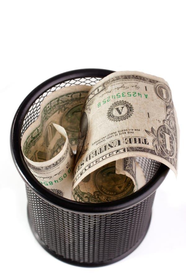 Dólares em um escaninho de lixo fotografia de stock