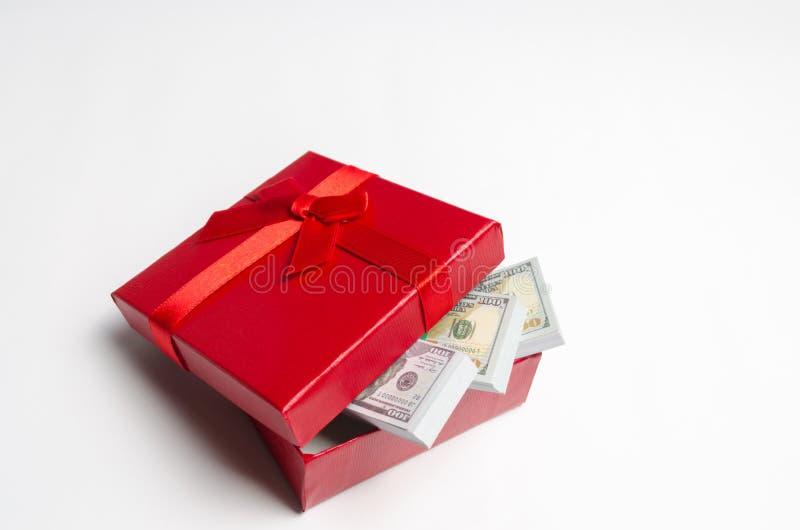 Dólares em uma caixa de presente vermelha em um fundo branco Busca para um presente para o feriado ilustração com curva vermelha  fotos de stock royalty free
