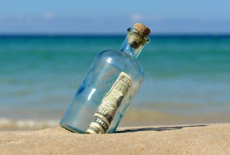 10 dólares em uma garrafa na praia imagem de stock