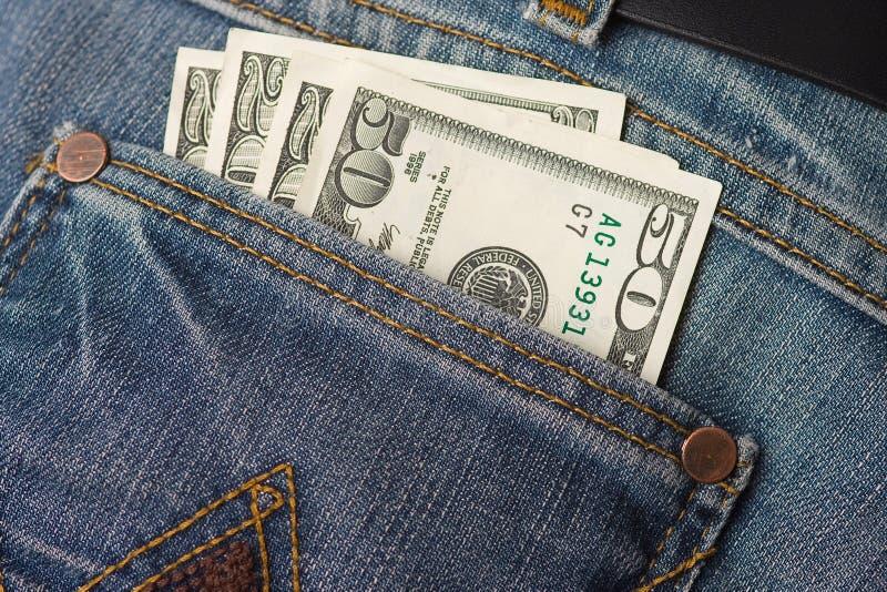 Dólares en bolsillo de los pantalones vaqueros foto de archivo
