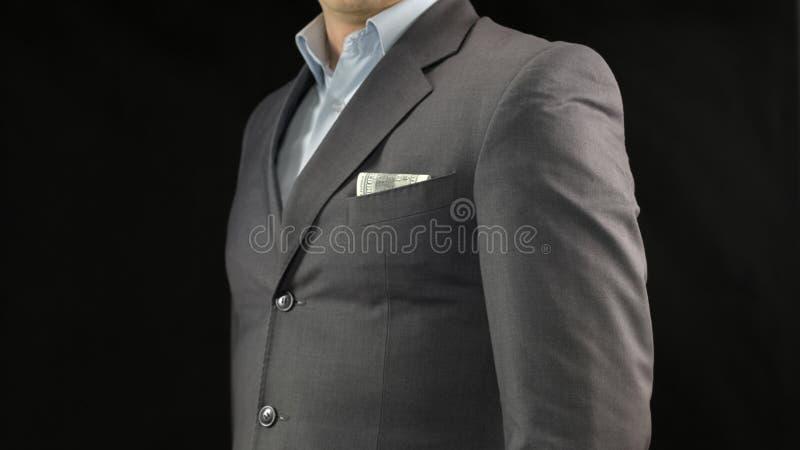 Dólares en bolsillo del traje del hombre de negocios, el ahorro del dinero, la renta o el concepto del soborno fotos de archivo