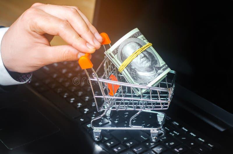 Dólares en la carretilla del supermercado en el teclado Compras en línea Comercio electrónico En Internet inversión del dinero en imagen de archivo libre de regalías
