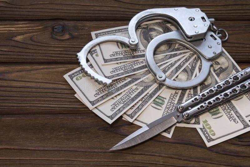 Dólares esposados del cuchillo y del dinero foto de archivo