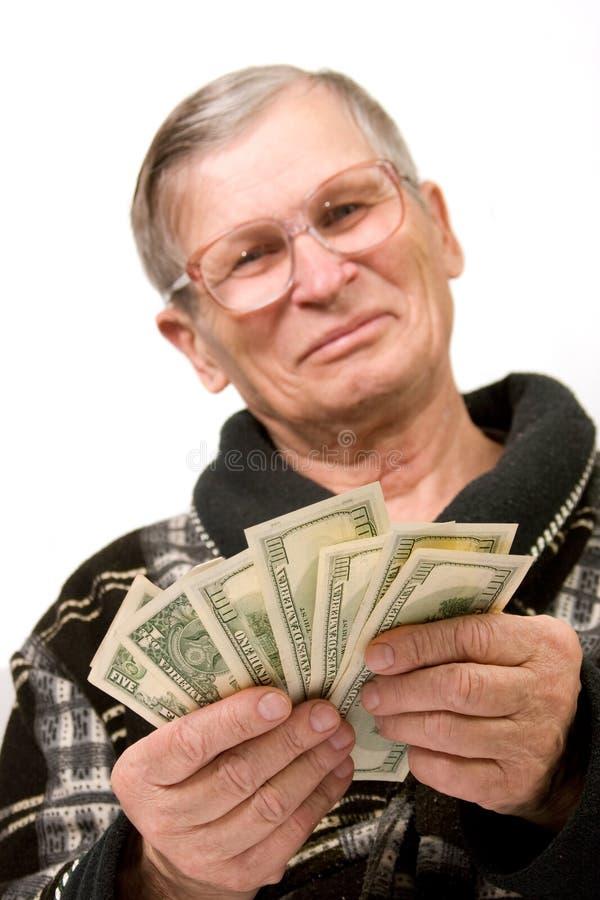 Dólares felizes da terra arrendada do homem idoso fotografia de stock