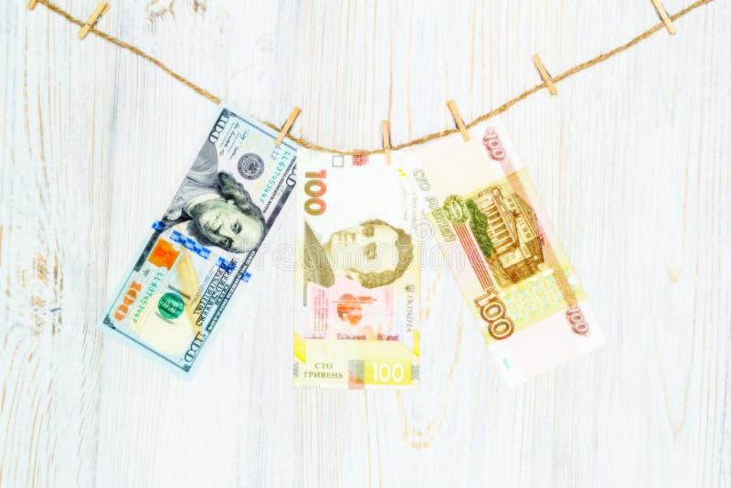 Dólares, hryvnia e rublos suspendidos em pregadores de roupa Lavagem de dinheiro, fraude da moeda e conceito da corrupção foto de stock