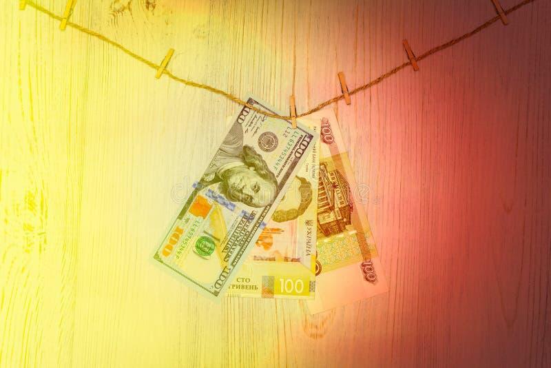 Dólares, hryvnia e rublos suspendidos em pregadores de roupa Lavagem de dinheiro, fraude da moeda e conceito da corrupção imagens de stock
