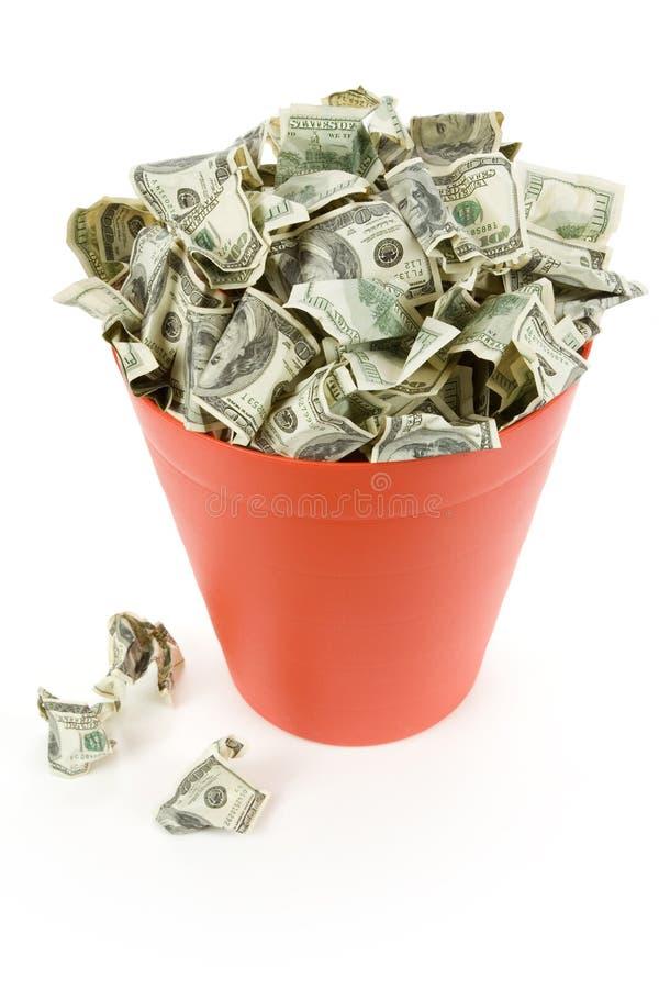 Dólares na lata de lixo vermelha imagens de stock