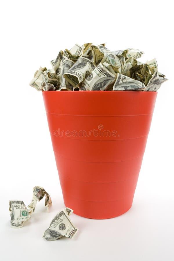 Dólares na lata de lixo vermelha fotografia de stock royalty free