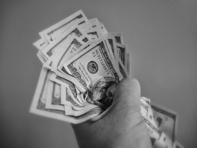 Dólares que asen de la mano fotografía de archivo