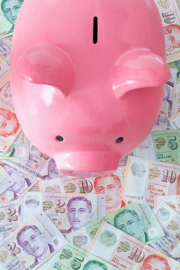 Dólares y hucha singapurenses Ahorro y dinero de depósito imagen de archivo