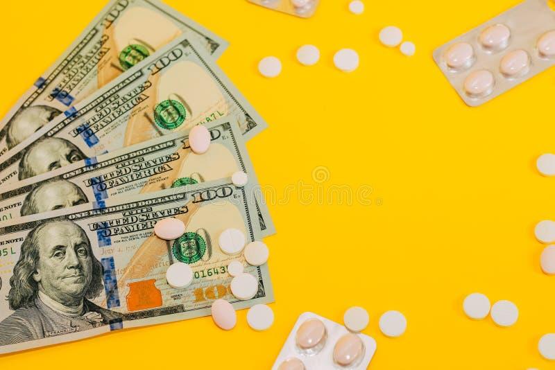 Dólares y píldoras en cierre amarillo del fondo para arriba imágenes de archivo libres de regalías