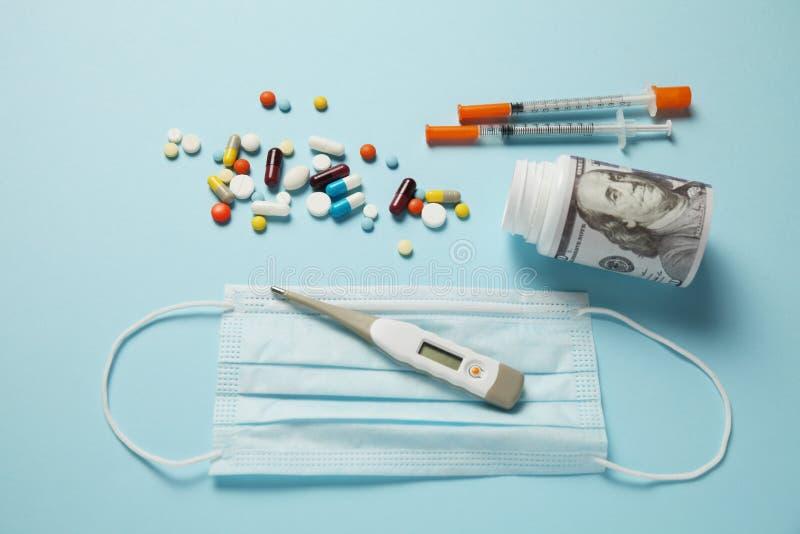 Dólares y píldoras en fondo azul Medicina costosa y seguro médico fotografía de archivo libre de regalías
