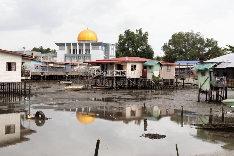 Dôme d'or de mosquée au-dessus du délabrement pauvre de village de pauvreté couru vers le bas photographie stock libre de droits