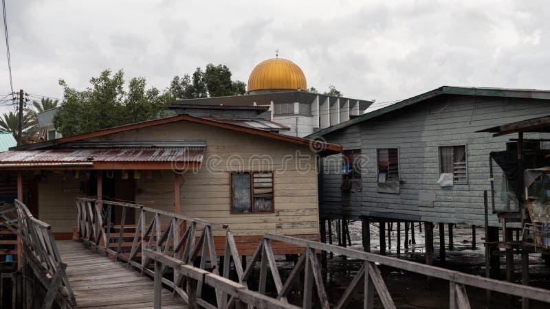 Dôme d'or de mosquée au-dessus du délabrement pauvre de village de pauvreté couru vers le bas images libres de droits