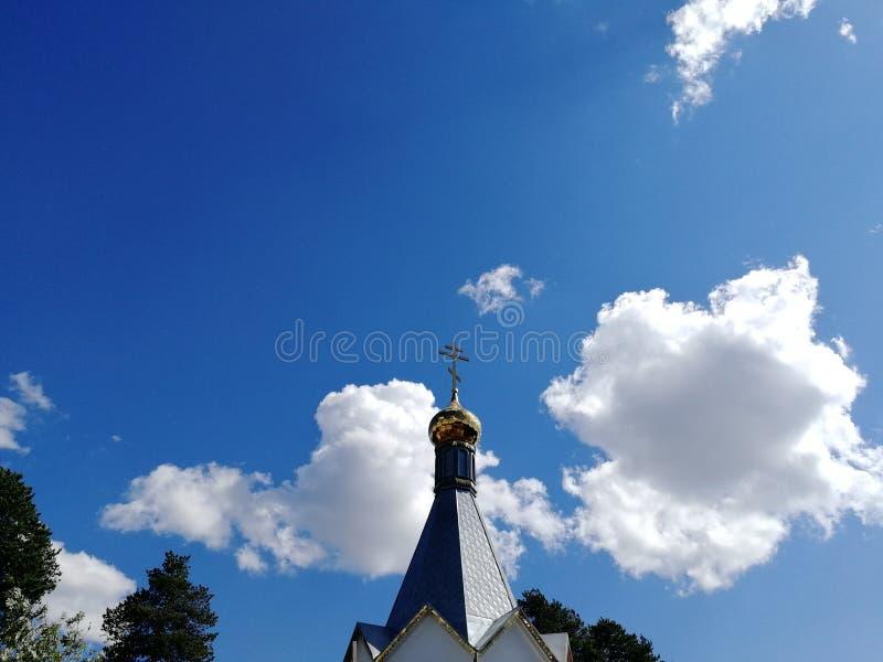 Dôme de l'église orthodoxe russe avec une croix contre le ciel bleu et les nuages blancs Près des dessus des arbres photographie stock