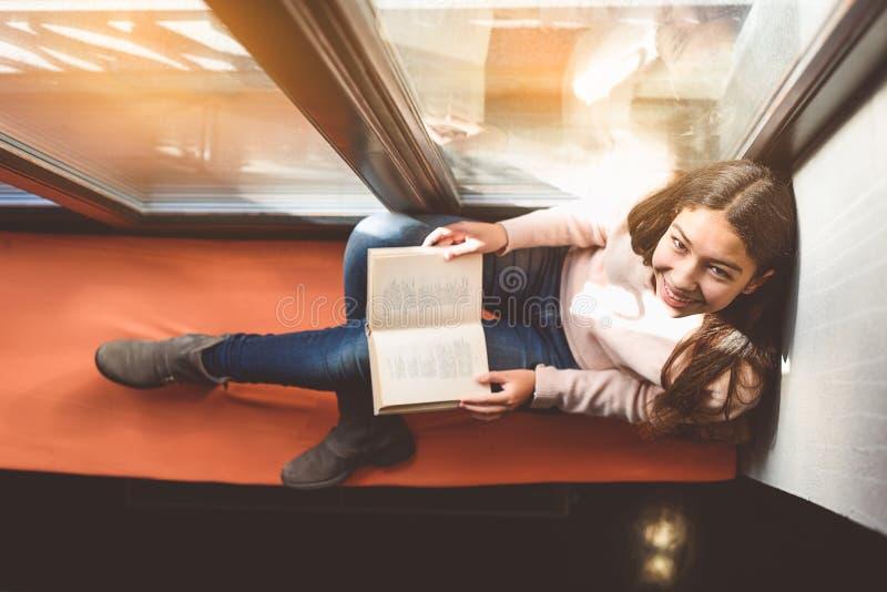 Dölja med boken på fönsterbräda arkivbild