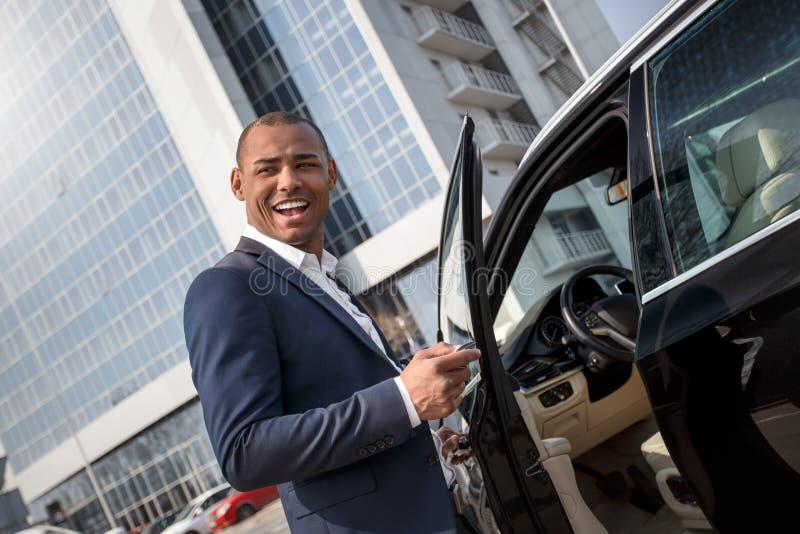 Dörr för bil för anseende för ung man öppnande med larmtangenten som åt sidan ser skämtsam royaltyfri foto