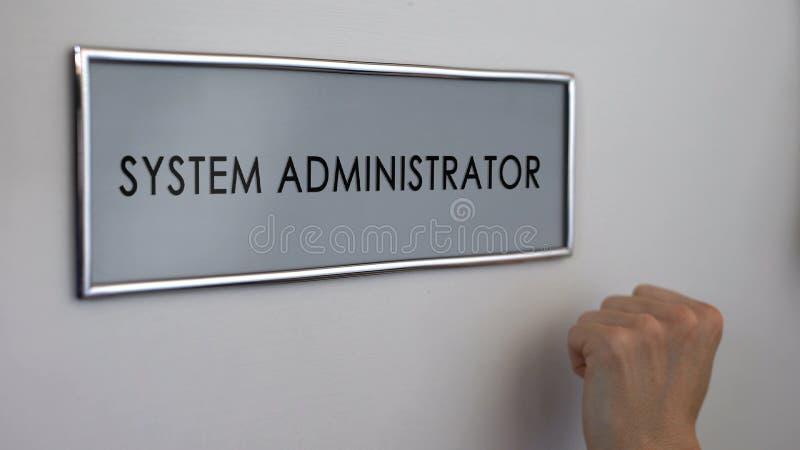 Dörr för kontor för systemadministratör, hand som knackar closeupen, datorspecialist royaltyfria bilder