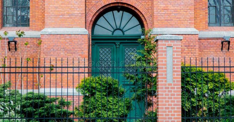 Dörr med bågen i gammal tegelstenbyggnad av den viktorianska eran royaltyfria bilder