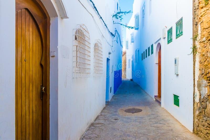 Dörr och härlig gata av vita forntida medina av den Asilah byn, Marocko arkivbilder