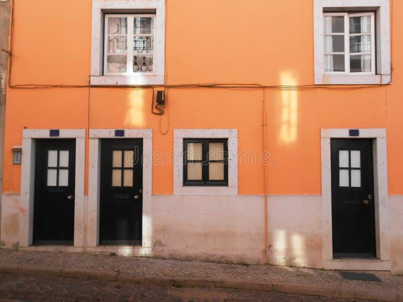DÖRRAR OCH WINDOWS PÅ DEN ORANGE FASADEN, LISSABON, PORTUGAL arkivbild