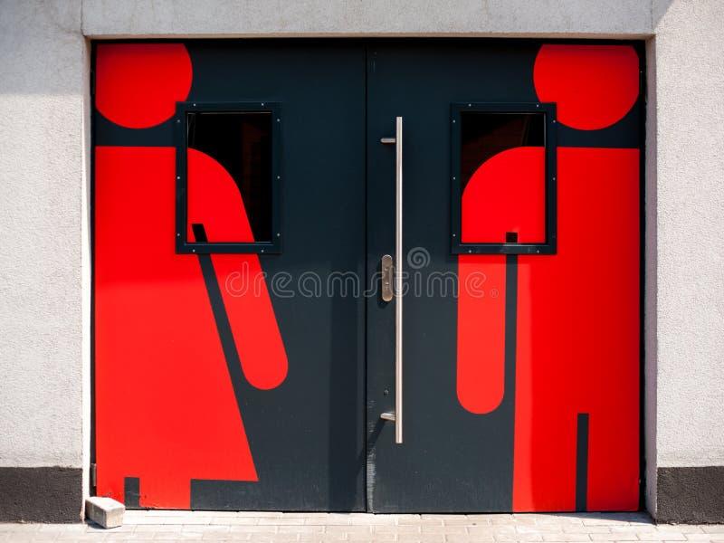 Dörrar till toaletten med tecken av mannen och kvinnlign royaltyfri foto