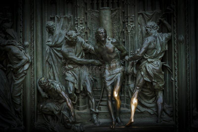 Dörren av den centrala ingången av Duomodomkyrkan av Milan med beståndsdelar av livet av Jesus royaltyfria foton
