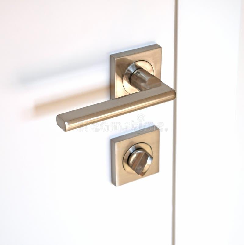 Dörren integrerade låset som består av ett roterande metallhandtag och en låsa apparat royaltyfria foton