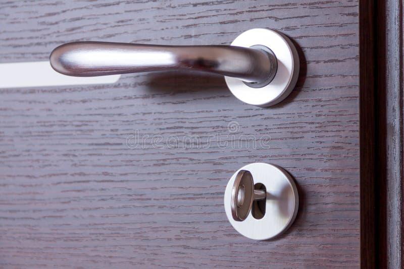 Dörrhandtag med tangenten i låset, dörrhandtaget av sovrumdörren, ingångsträdörr royaltyfria foton