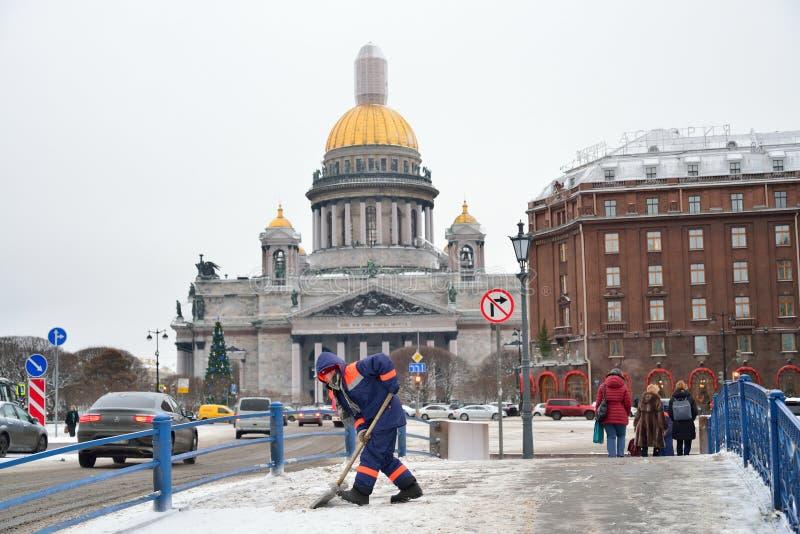 Dörrvaktarbetaren tar bort insnöat mitten av St Petersburg royaltyfri fotografi