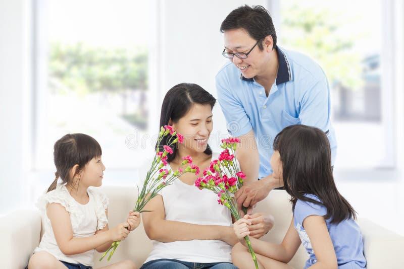 Döttrar och fader som firar moders dag arkivfoton